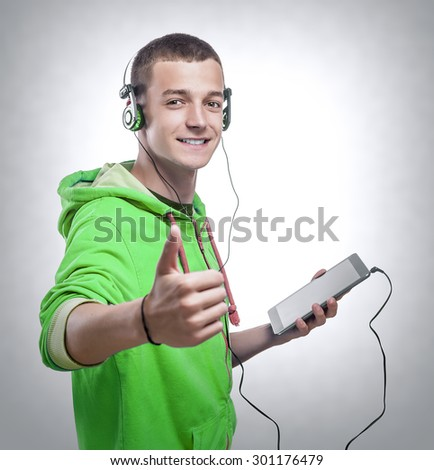 Handsome guy using tablet pc with headphones showing thumbs up. Isolated on white. - stock photo