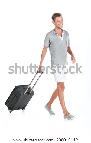 handsome guy walking with luggage and smiling. profile of man pulling bag on white background - stock photo