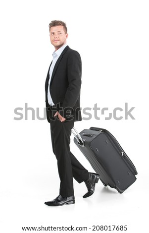 handsome guy walking with luggage and smiling. side view of young man on white background - stock photo