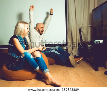 handsome guy win a computer game from his girlfriend. concept of leisure entertainment and fun - stock photo