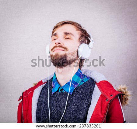 handsome guy with a beard listening to music - stock photo