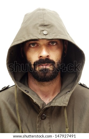 Handsome guy with beard and military jacket with hood on white background