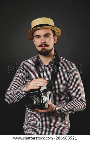 handsome guy with beard and mustache with vintage camera on dark background in studio