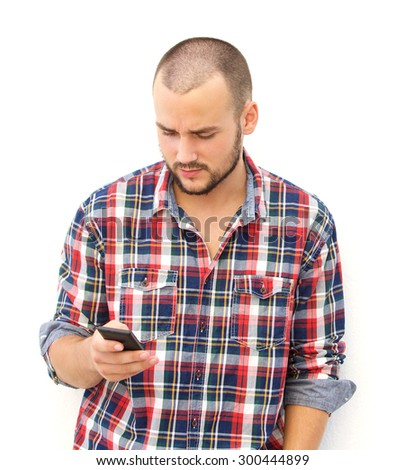 Handsome guy with beard searching his smart phone - stock photo