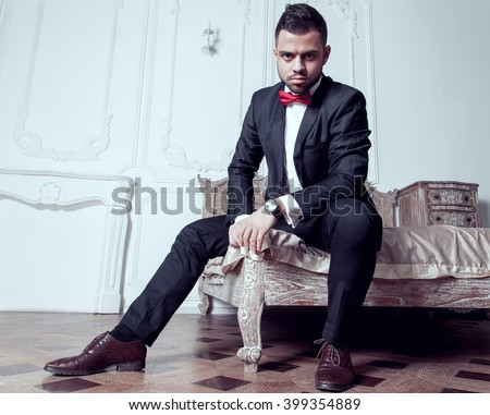 Handsome guy with beard, side whiskers and mustache sits on a bed dressed in black suit, white shirt, red bow-tie and brown leather shoes - stock photo