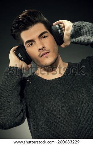 Handsome guy with headphones over grey background - stock photo