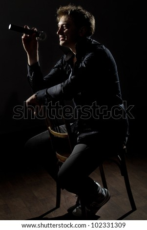 Handsome guy with microphone in hands sitting on chair