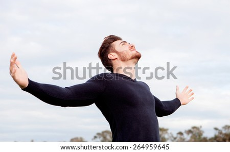 Handsome guy with open arms relaxed in the field - stock photo