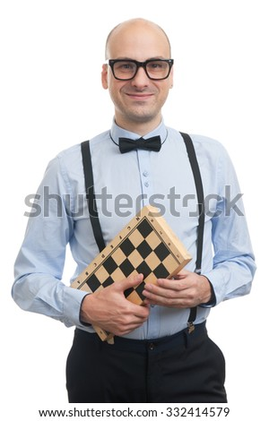 Handsome guy with suspenders and bow-tie holding chess board - stock photo
