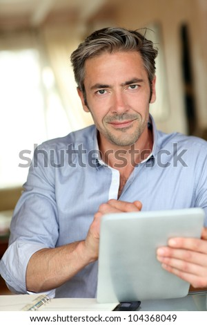 Handsome guy working from home with electronic tablet - stock photo