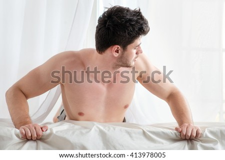 Handsome half-naked man lying on the bed and looking a side.
