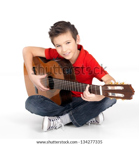 Handsome happy  boy is playing on acoustic guitar - isolated on white background - stock photo