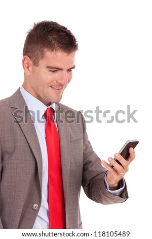 Handsome happy business man reading an SMS on smartphone against white background - stock photo