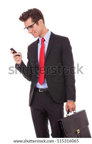 Handsome happy business man reading an SMS on smartphone while holding his briefcase, against white background - stock photo