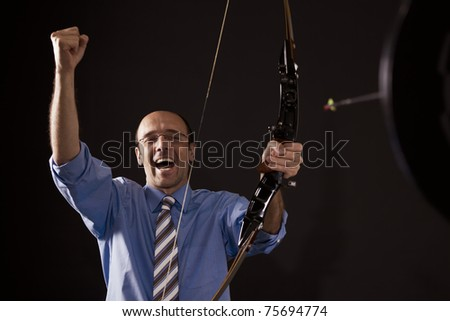 Handsome happy businessman cheering as he hit the target with bow and arrow symbolizing successful business.