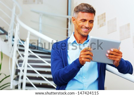 Handsome happy businessman with electronic tablet - stock photo