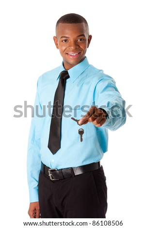 Handsome happy corporate business man realtor handing over keys to new house, dressed in blue shirt and black tie, isolated. Selling concept.