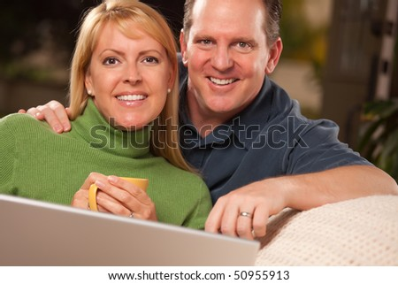 Handsome Happy Couple Using Their Laptop Together. - stock photo