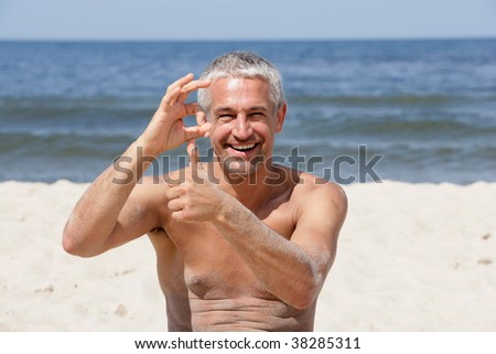 Handsome happy man giving thumbs up and OK sign on the beach - stock photo