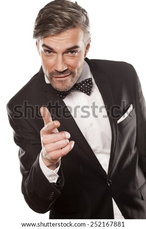 handsome happy man in black jacket pointing a finger at you - stock photo
