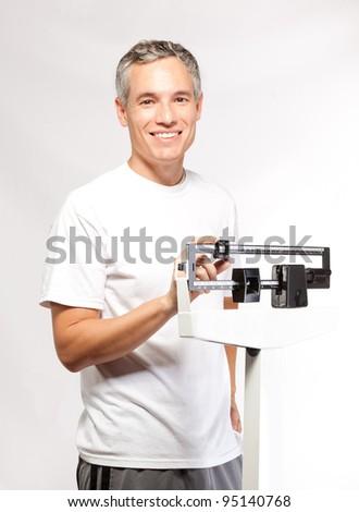 Handsome happy man on scale - stock photo