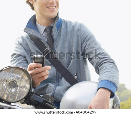 Handsome happy man sitting on the motorbike holding the phone - stock photo