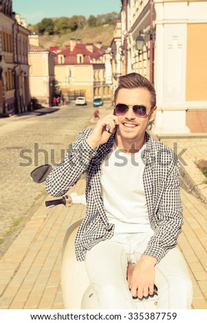 Handsome happy man sitting on the motorbike talking on the phone - stock photo