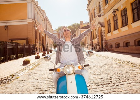 Handsome happy man with glasses riding a motorbike with both hands raised up - stock photo