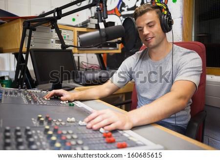 Handsome happy radio host moderating in studio at college - stock photo