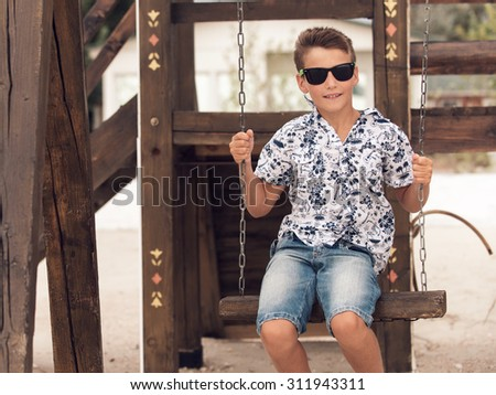 Handsome happy smiling adolescent boy in sunglasses  on a swing - stock photo