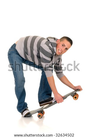 Handsome happy smiling blushing skaterboy dressed in jeans, studio shot - stock photo