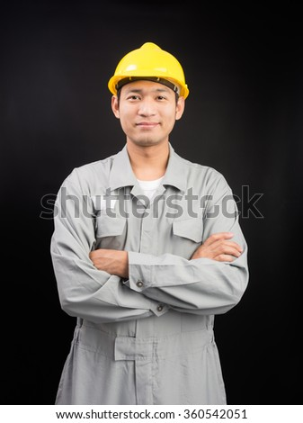 Handsome happy supervisor or technician worker on black background - stock photo