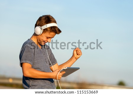 Handsome happy teen boy listening to music on digital tablet outdoors.