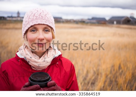 Handsome Happy Woman in a Field during cold Autumn Day with a Coffee - stock photo