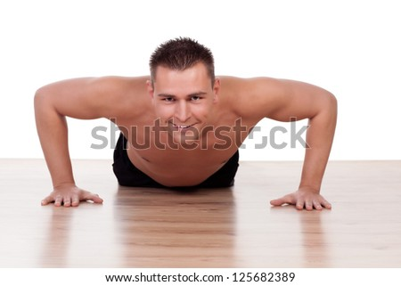 Handsome healthy fit young man doing press ups on a gym floor looking at the camera with a cheerful smile