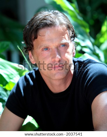 Handsome, healthy middle aged man looking thoughtfully in the sun and smiling - stock photo