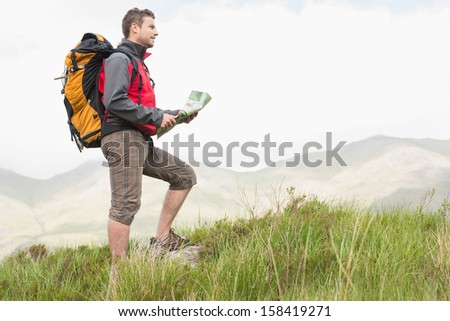 Handsome hiker with backpack hiking uphill holding a map in the countryside - stock photo