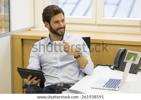 Handsome hipster bearded businessman working in office on computer - stock photo