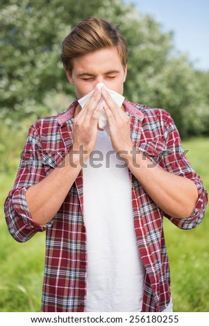 Handsome hipster blowing his nose on a sunny day - stock photo