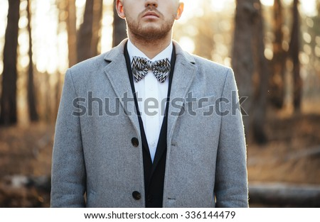 Handsome hipster businessman wearing a suit, standing in the sunset forest, cropped photo
