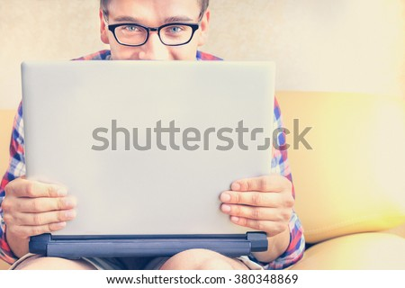 Handsome hipster guy is hiding behind his laptop computer in his hands. Man in glasses laughing with computer, concept of new trends and technology in everyday lifestyle. Main focus on the hand. - stock photo
