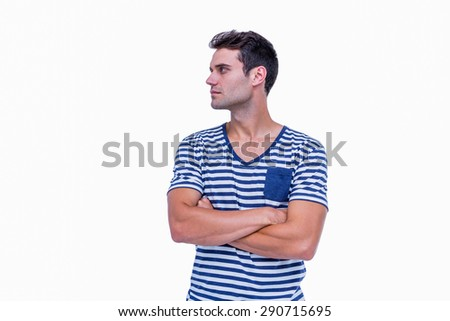 Handsome hipster looking away with arms crossed on white background