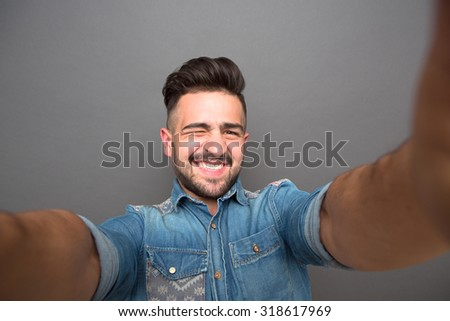 Handsome hipster man winking and making selfies isolated on grey background. Man with elegant hair happy smiling for the camera. - stock photo