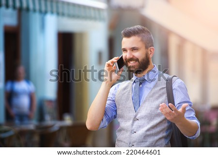 Handsome hipster modern businessman with beard walking in town and calling on mobile phone - stock photo