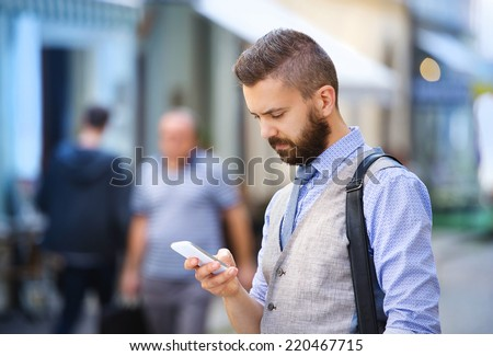 Handsome hipster modern businessman with beard walking in town with mobile phone - stock photo