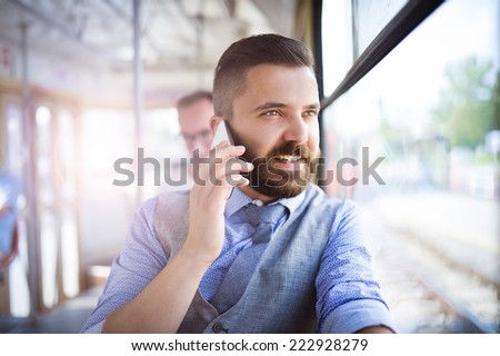 Handsome hipster modern man calling by mobile phone in tram - stock photo