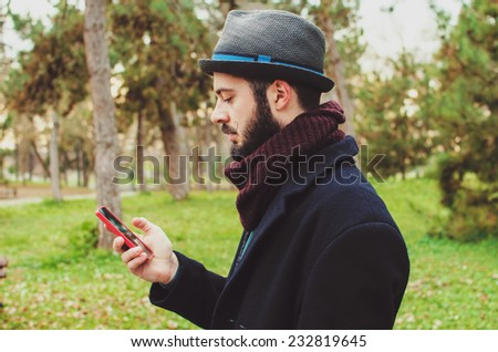 Handsome hipster modern man using smart phone in the park - stock photo