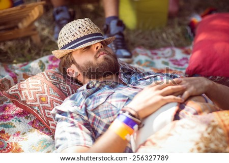 Handsome hipster relaxing on campsite at a music festival - stock photo