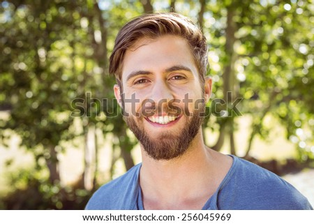 Handsome hipster smiling at camera on a summers day