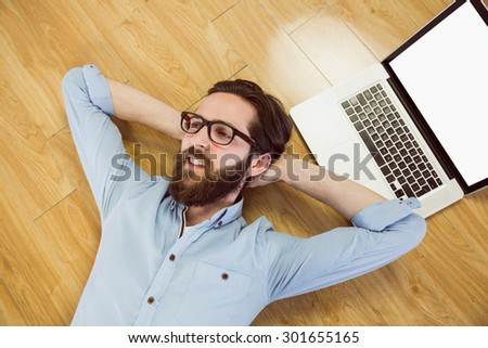 Handsome hipster using his laptop on wooden floor - stock photo